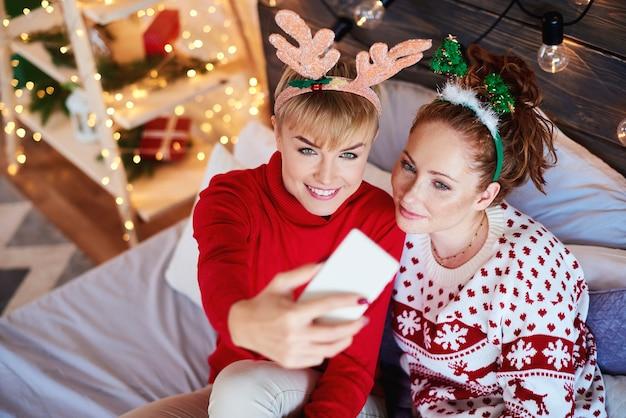 Zwei mädchen, die selfie im schlafzimmer nehmen