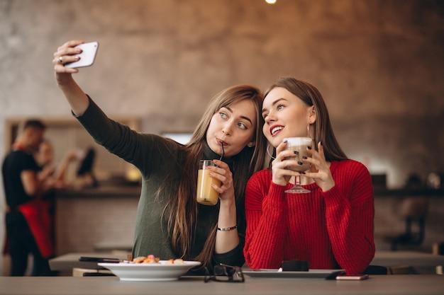 Zwei mädchen, die selfie in einem café tun