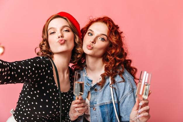Zwei mädchen, die selfie mit weingläsern nehmen. studioaufnahme von freunden, die champagner auf rosa hintergrund trinken.