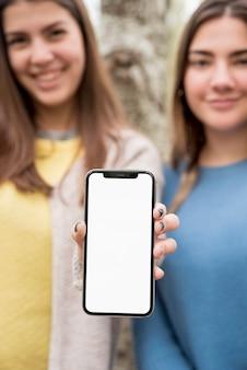 Zwei mädchen, die smartphonemodell darstellen
