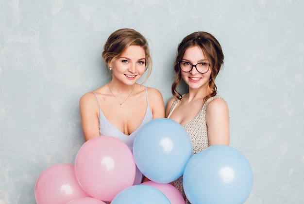 Zwei mädchen, die spaß in einem studio haben und mit blauen und rosa luftballons spielen.