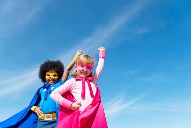 Zwei mädchen, die superhelden spielen