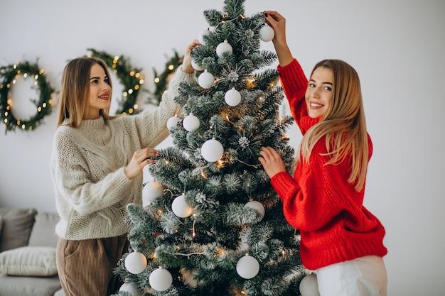 Zwei mädchen, die weihnachtsbaum schmücken