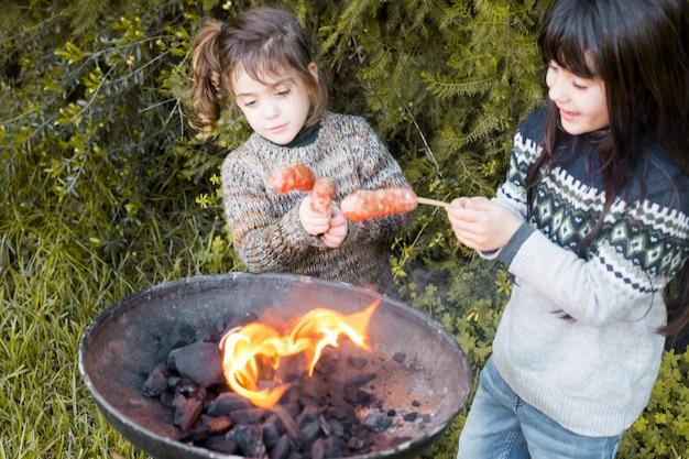 Zwei mädchen, die würste auf grill im park brennen