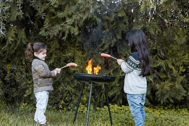 Zwei mädchen, die würste im grill grillen