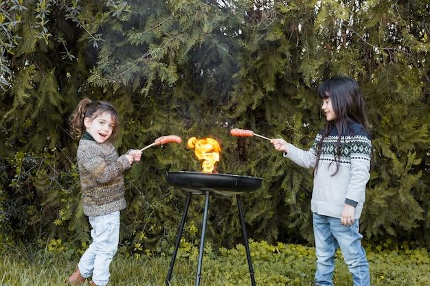 Zwei mädchen, die würste im grill vorbereiten