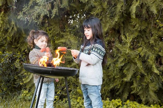 Zwei mädchen, die würste im park brät