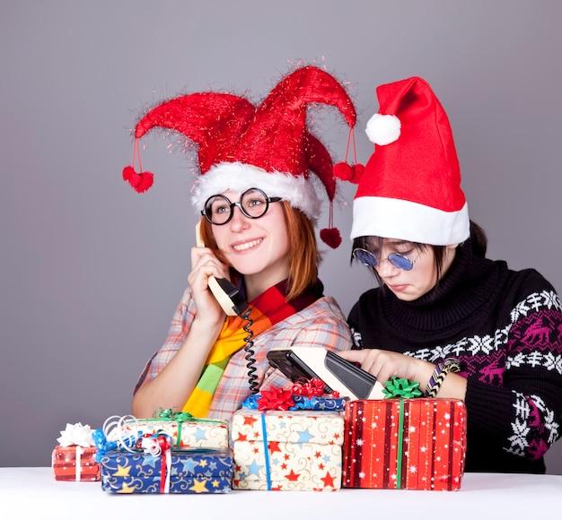 Zwei mädchen, die zum weihnachtsmann für besseres weihnachtsgeschenk rufen. studioaufnahme.