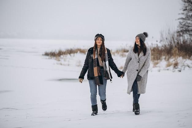 Zwei mädchen, die zusammen in einen winterpark gehen