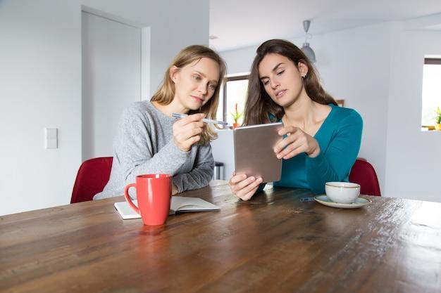 Zwei mädchen, die zusammen online kaufen