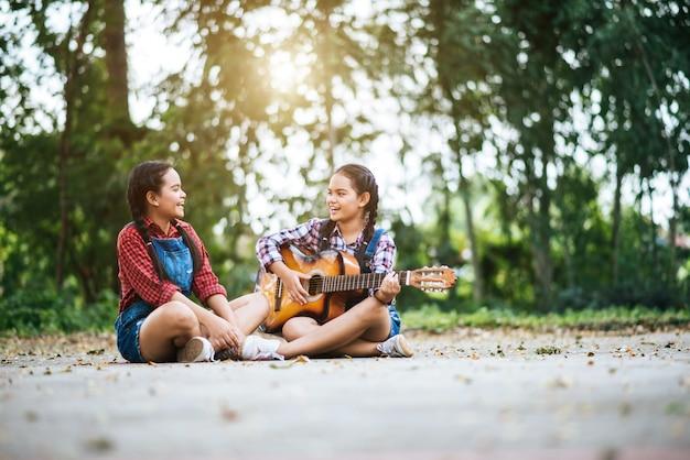 Zwei mädchen entspannen sich, gitarre spielend und singen ein lied
