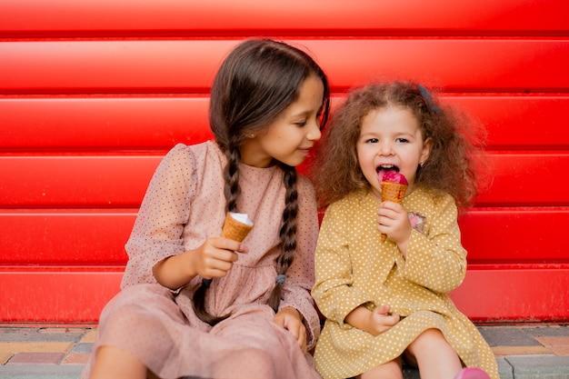 Zwei mädchen essen eis und spielen herum. ein teenager und ein kleines mädchen auf einem roten wandhintergrund.
