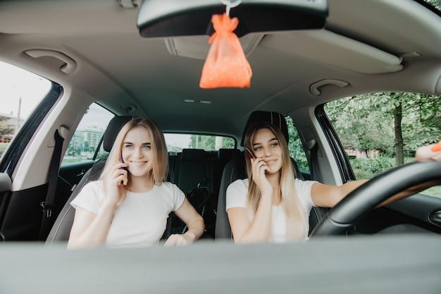 Zwei mädchen fahren auto, während sie am telefon sprechen. ausflug.
