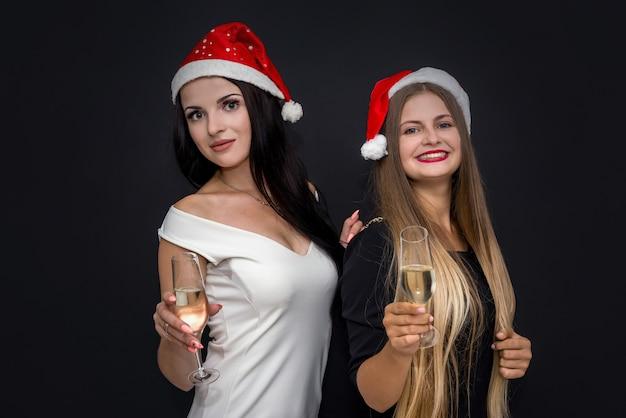 Zwei mädchen feiern neujahr in weihnachtsmützen