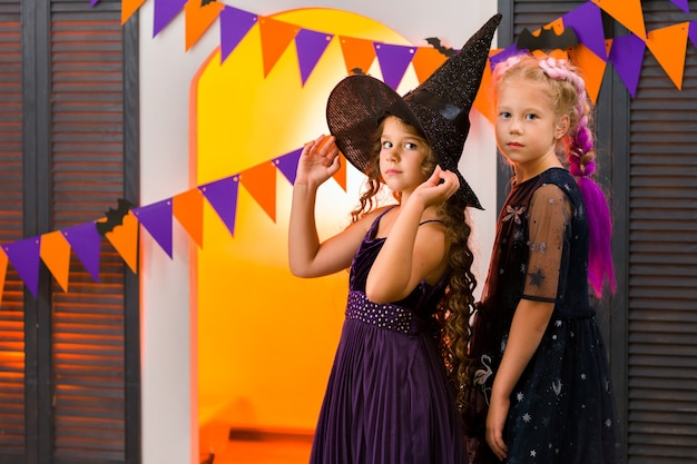 Zwei mädchen gegen eine girlande aus orange und lila fahnen, die an der wand hängen