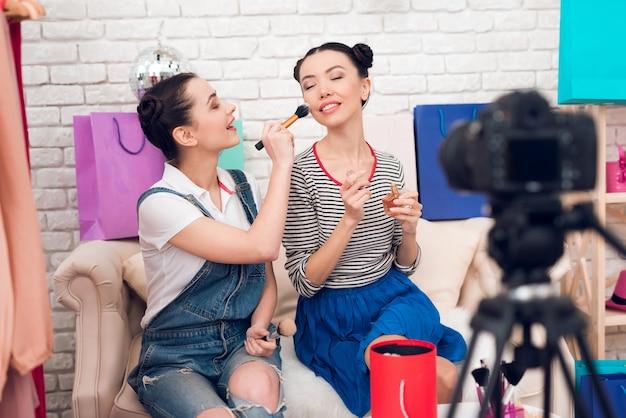 Zwei mädchen halten pinsel und parfüm zur kamera