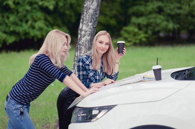Zwei mädchen hielten auf der straße an, um anweisungen zu erhalten und kaffee zu trinken