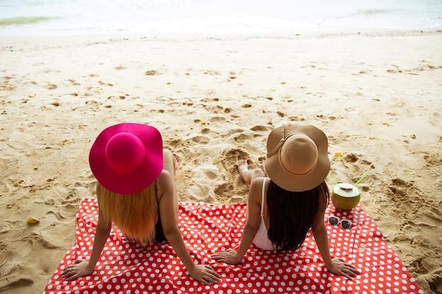Zwei mädchen im bikini, in den sommerferien und im urlaub - mädchen, die am strand ein sonnenbad nehmen