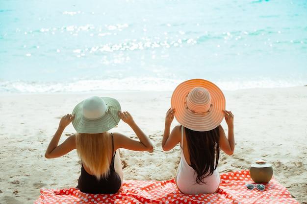 Zwei mädchen im bikini, sommerferien und ferien - mädchen, die am strand ein sonnenbad nehmen