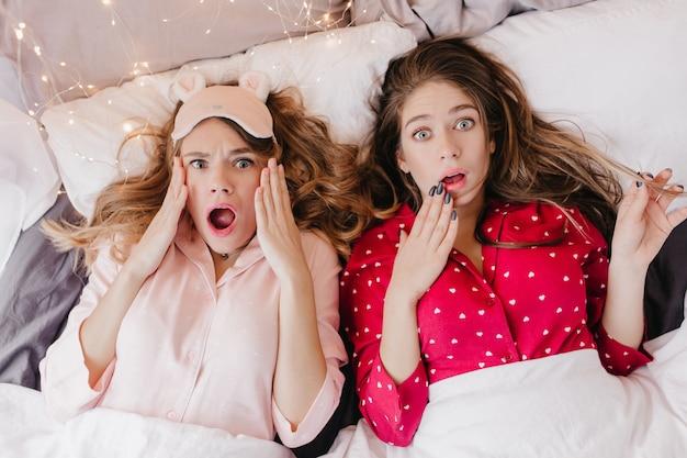 Zwei mädchen im niedlichen schlafanzug, der erstaunen ausdrückt. überkopfporträt der schockierten damen, die unter der decke liegen.