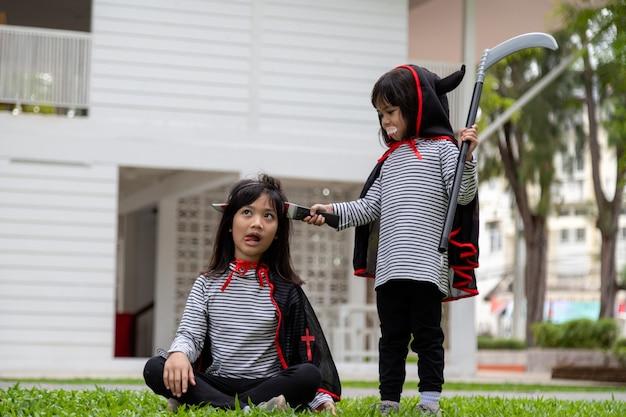 Zwei mädchen im park mit halloween-kostümen, die spaß haben
