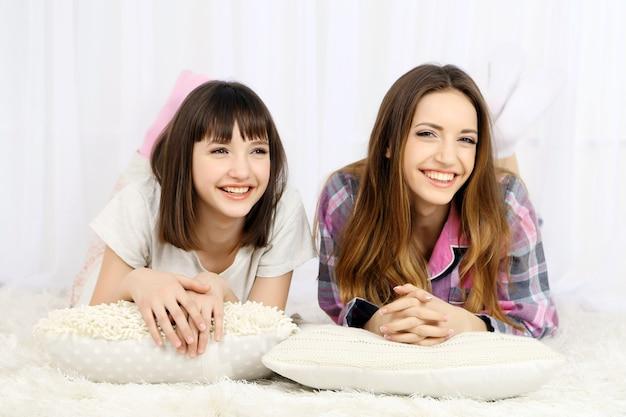 Zwei mädchen im pyjama liegen auf einem flauschigen weißen teppich auf grau