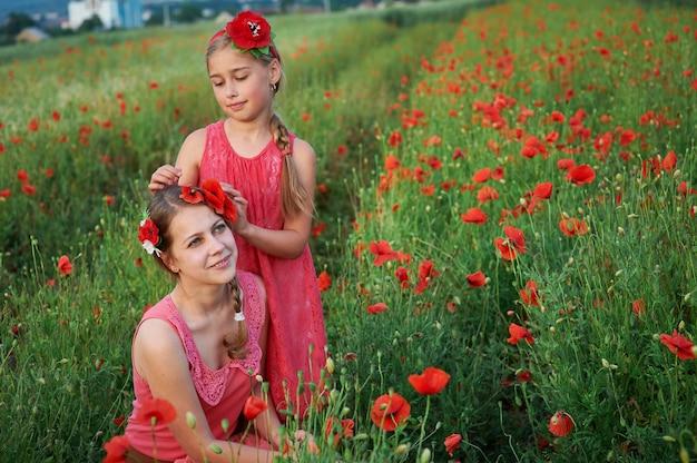 Zwei mädchen im roten kleid gehend auf mohnblumenfeld