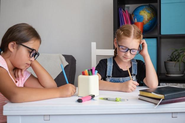 Zwei mädchen in brillen lernen zu hause, machen hausaufgaben. schreiben. streber. zurück zum schulkonzept.
