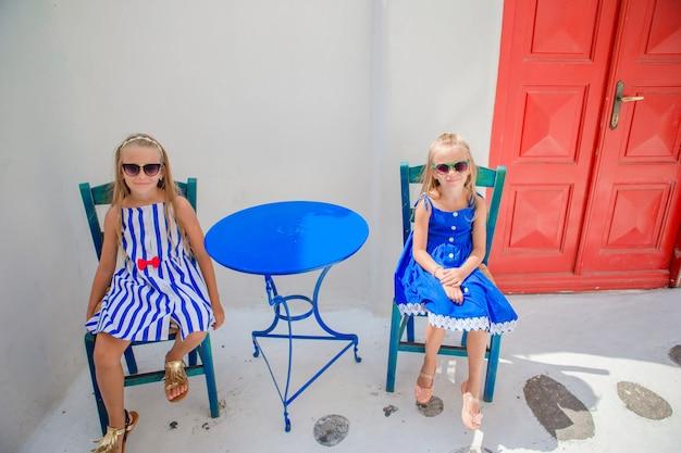 Zwei mädchen in den blauen kleidern, die café im im freien auf straße des typischen griechischen dorfs auf mykonos-insel, griechenland sitzen