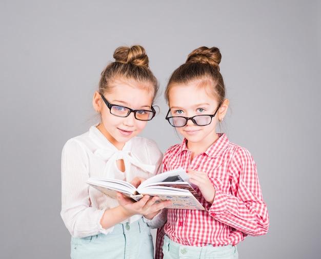 Zwei mädchen in den gläsern, die mit buch stehen