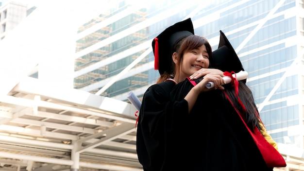 Zwei mädchen in den schwarzen kleidern und halten die diplombescheinigung, die mit glücklichem absolvent sitzt und lächelt.