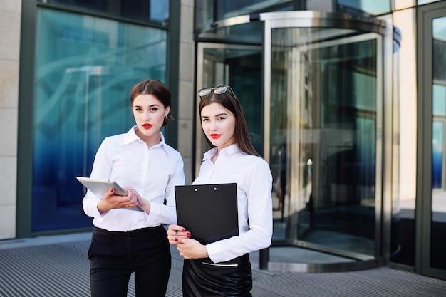Zwei mädchen in der geschäftskleidung auf dem hintergrund eines bürogebäudes