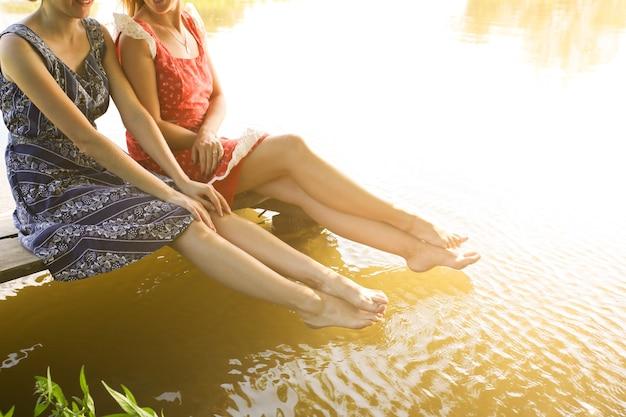 Zwei mädchen in der nähe von fluss in vintage-kleidern. barfüßige frauen, die urlaub genießen. rustikale sommerwohnung. freunde lifestyle-konzept. holzbrücke.