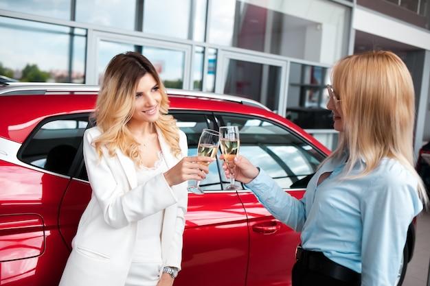 Zwei mädchen in einem autohaus trinken champagner