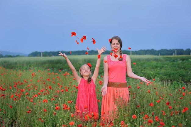 Zwei mädchen in einem roten kleid im frühjahr gehend auf das mohnblumenfeld