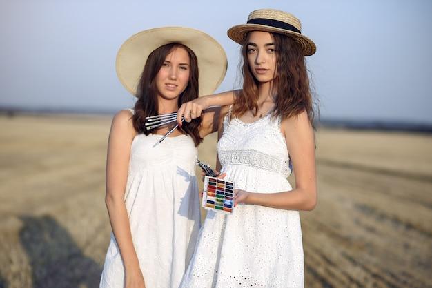 Zwei mädchen in einem weißen kleidermalerei auf einem gebiet