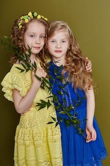 Zwei mädchen in hellen frühlingskleidern an einer olivfarbenen wand
