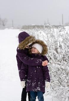 Zwei mädchen in identischen jacken stehen und plaudern bei schneefall auf einem schneebedeckten feld, schauen sich an und lächeln