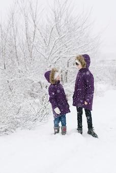 Zwei mädchen in identischer winterwarmer kleidung stehen während eines schneefalls auf einem schneebedeckten feld und schauen sich an
