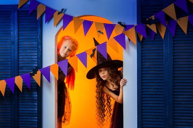 Zwei mädchen in karnevalskostümen blicken überrascht hinter einer girlande aus orangefarbenen und lila fahnen hervor.
