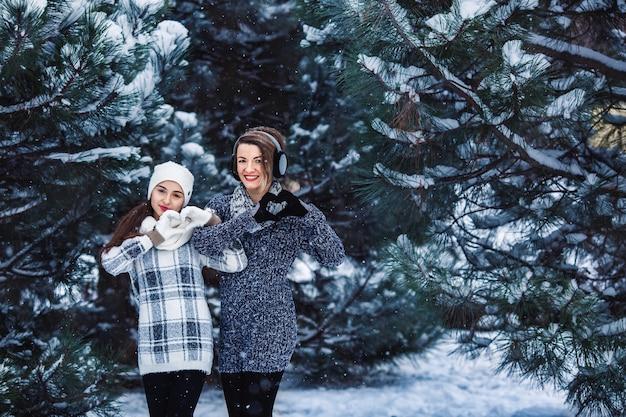 Zwei mädchen in pullovern und handschuhen im winter im wald. im winter schneit es im wald. mutter und tochter auf der straße bei schneewetter.
