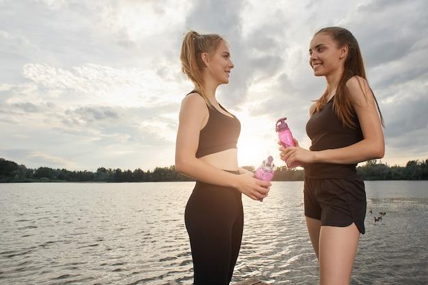 Zwei mädchen in sportkleidung kommunizieren im hintergrund des sees miteinander