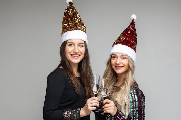 Zwei mädchen in weihnachtsmützen mit alkoholischen getränken.