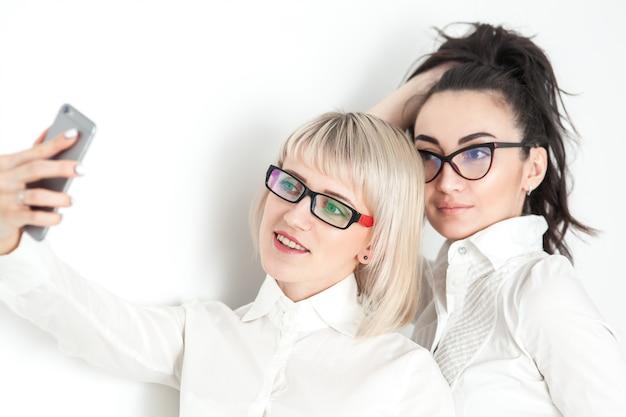 Zwei mädchen in weißen hemden und brillen machen selfies am telefon
