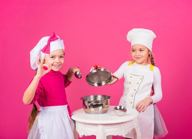 Zwei mädchen kocht mit dem topf, der okaygeste zeigt