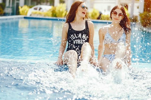 Zwei mädchen lachen und spaß am pool