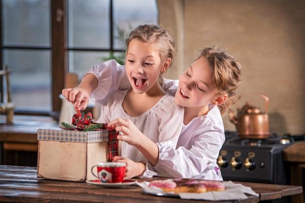 Zwei mädchen lösen fröhlich das band an der geschenkbox in der gemütlichen küche zu hause