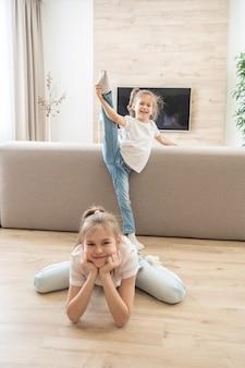 Zwei mädchen machen dehnübungen im wohnzimmer zu hause. freundliches schwesternkonzept