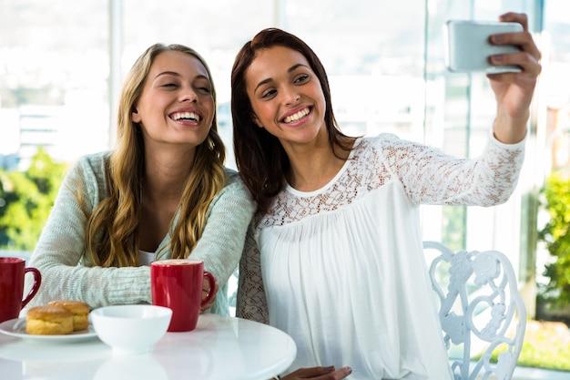 Zwei mädchen machen ein selfie, während sie essen und tee trinken