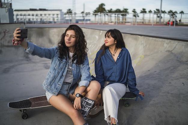 Zwei mädchen machen selfie im skatepark